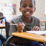 Disabled pupil smiling at camera in classroom